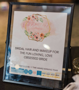 A sign reading: Bridal and makeup for the fun loving, love obsessed bride