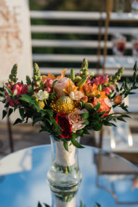 orange yellow red and pink flowers in a vase
