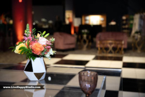 flowers in a checked vase with a checkered dance floor in the background