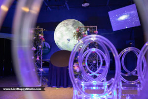 clear chairs with a moon and flowers in the background