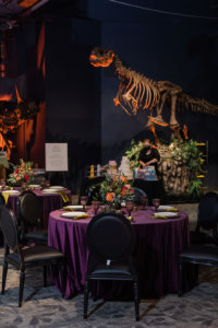 a wedding table with place settings and flowers in front of a dinosaur