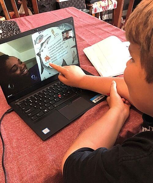 A kid watches a virtual science lesson
