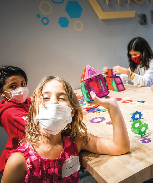 Three children doing STEM activity during a birthday party at Orlando Science Center