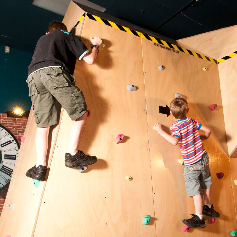 a man and two children climb a rock wall