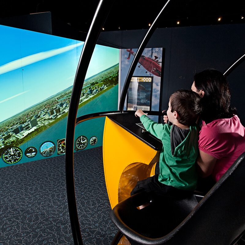 A caregiver and small child fly in the helicopter simulator.