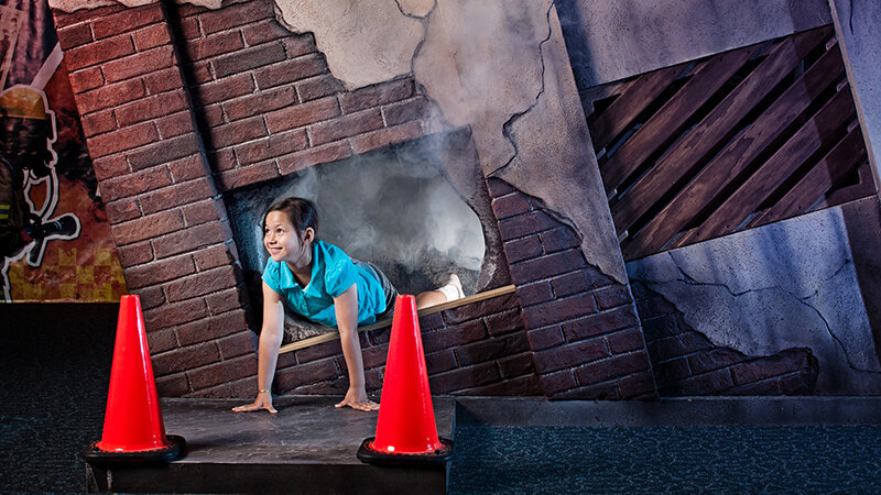 a girl crawling out of a simulated burning building