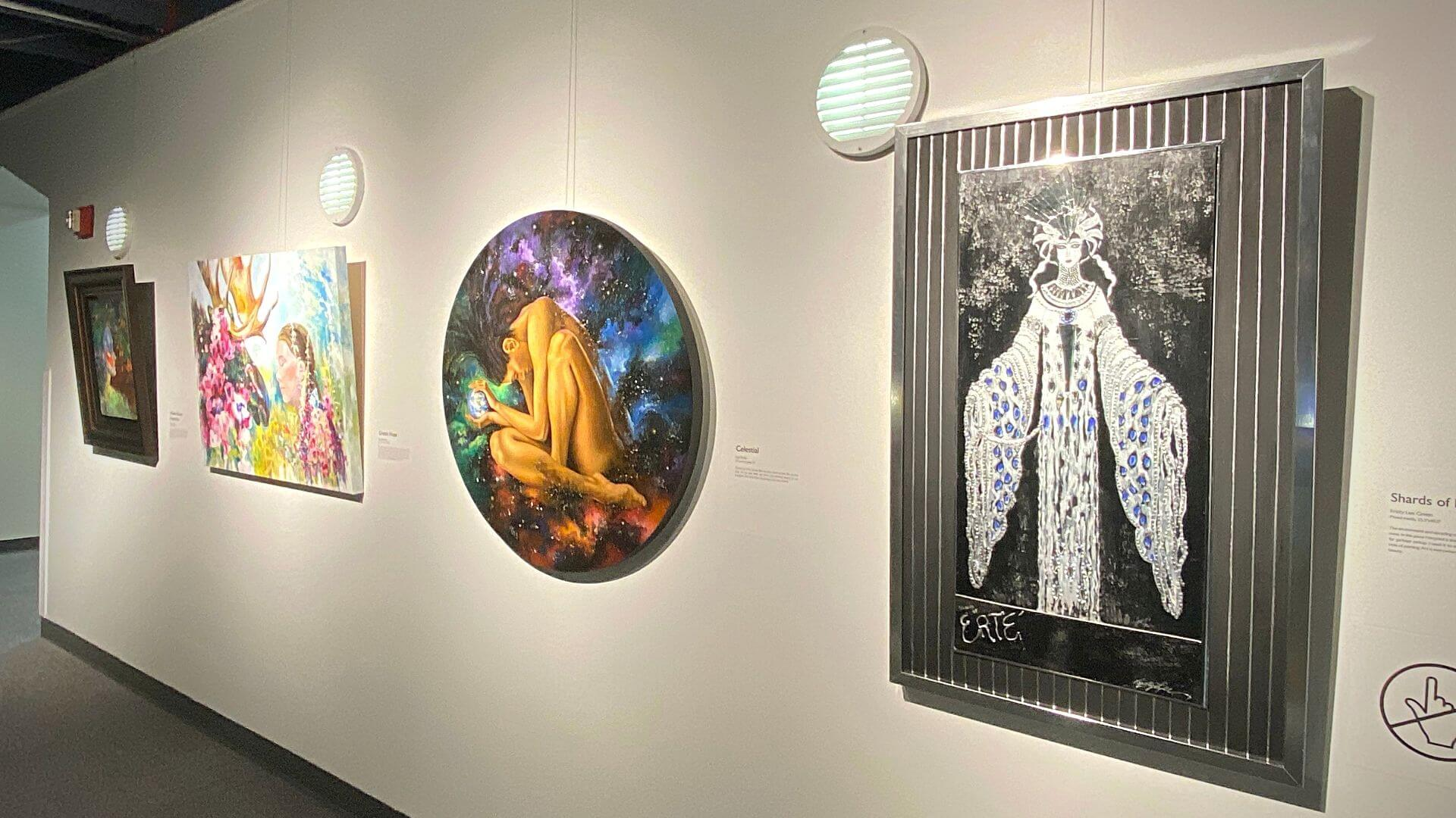 A gallery wall with a row of paintings about the environment