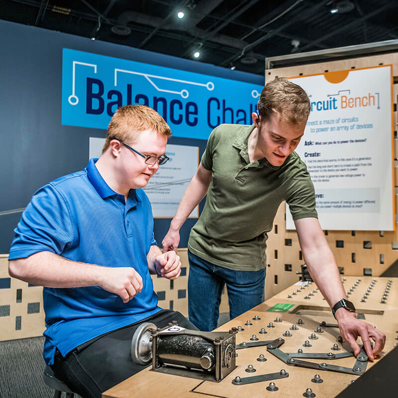 Two guests work together at the Circuit Bench exhibit in Kinetic Zone.