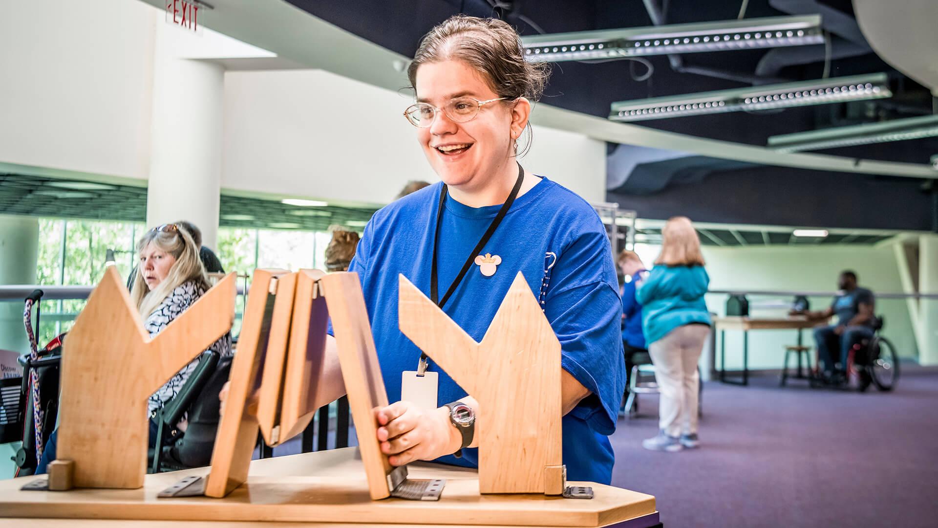 Volunteer interacts with a bridge-building exhibit at Orlando Science Center.