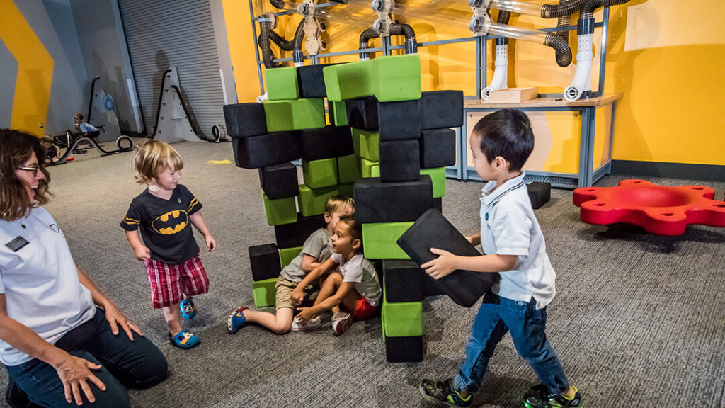 Children building with foam blocks in exploration-based early childhood exhibit