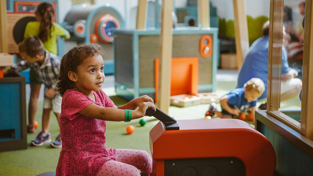 Child on small tractor in Orange Grove exhibit at Orlando Science Center