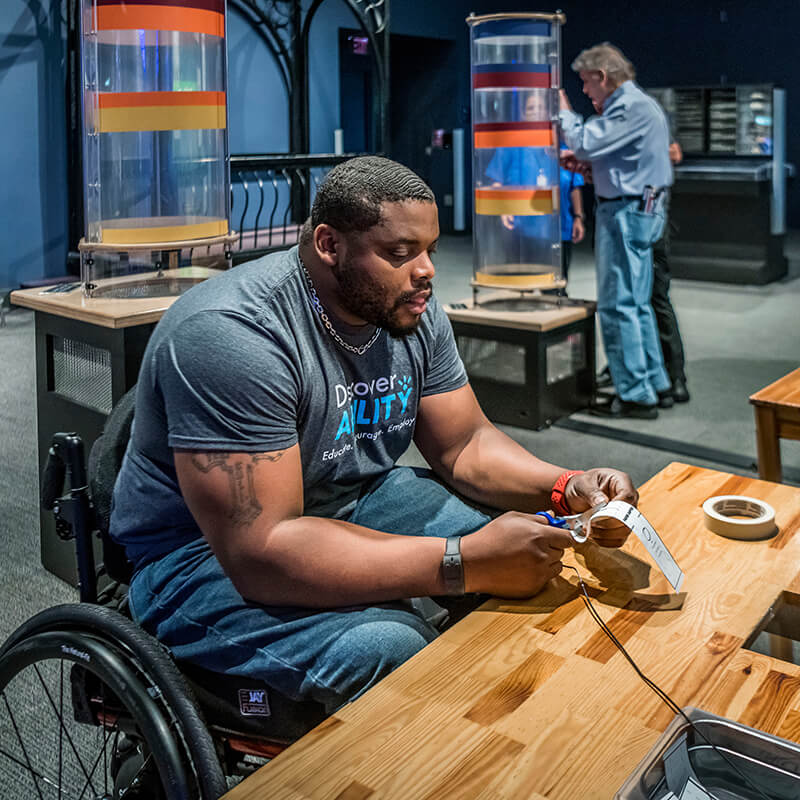 Guest travelling in a wheelchair builds a paper spinner to test in the wind tubes exhibit in Our Planet.