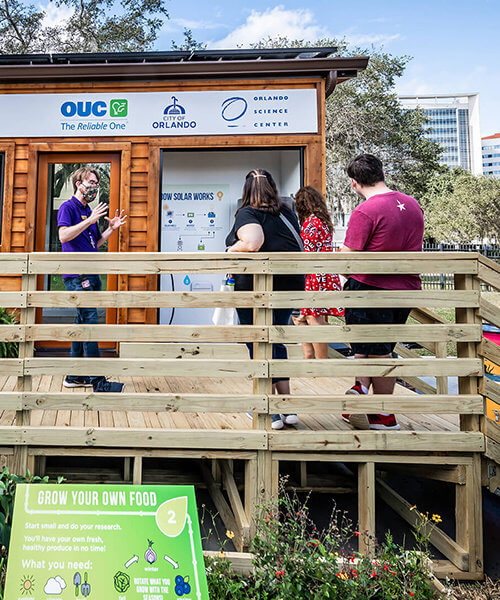 OSC staff member talking to a group of people looking at the tiny green home.