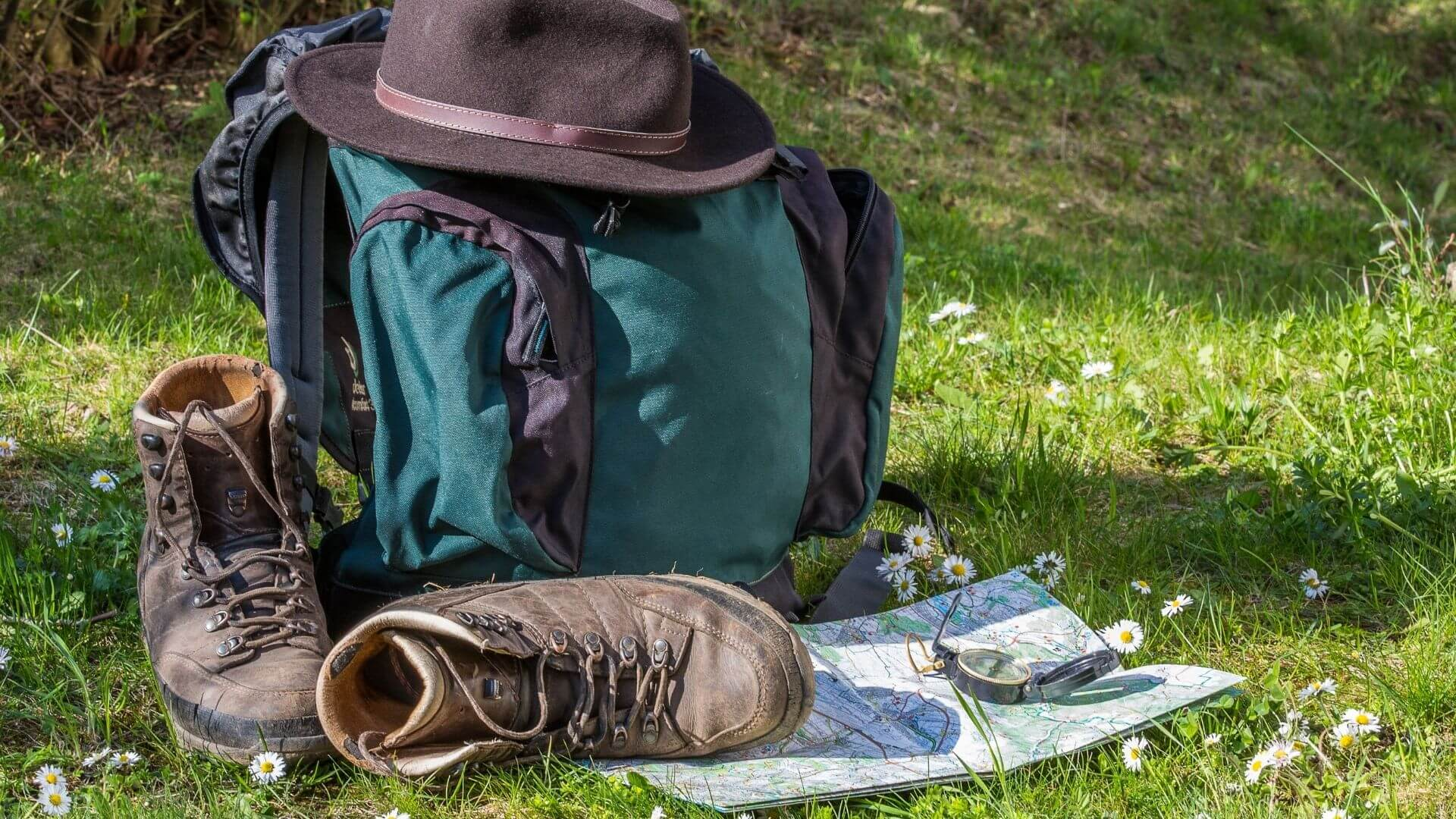 a backpack with boots and a map and a compass and a hat