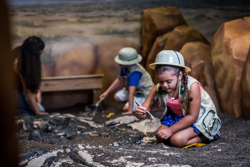 a little girl digging up fake dinosaur bones