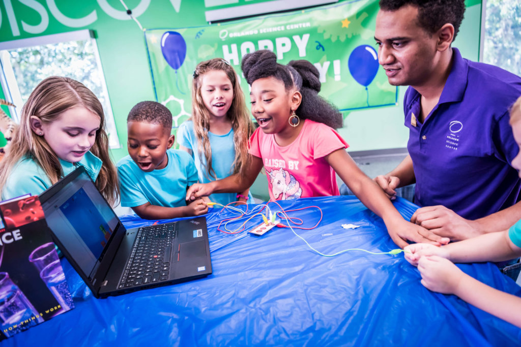 a group of kids at a birthday party doing a computer project