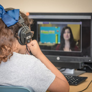 Young student engaged in virtual education at a computer.