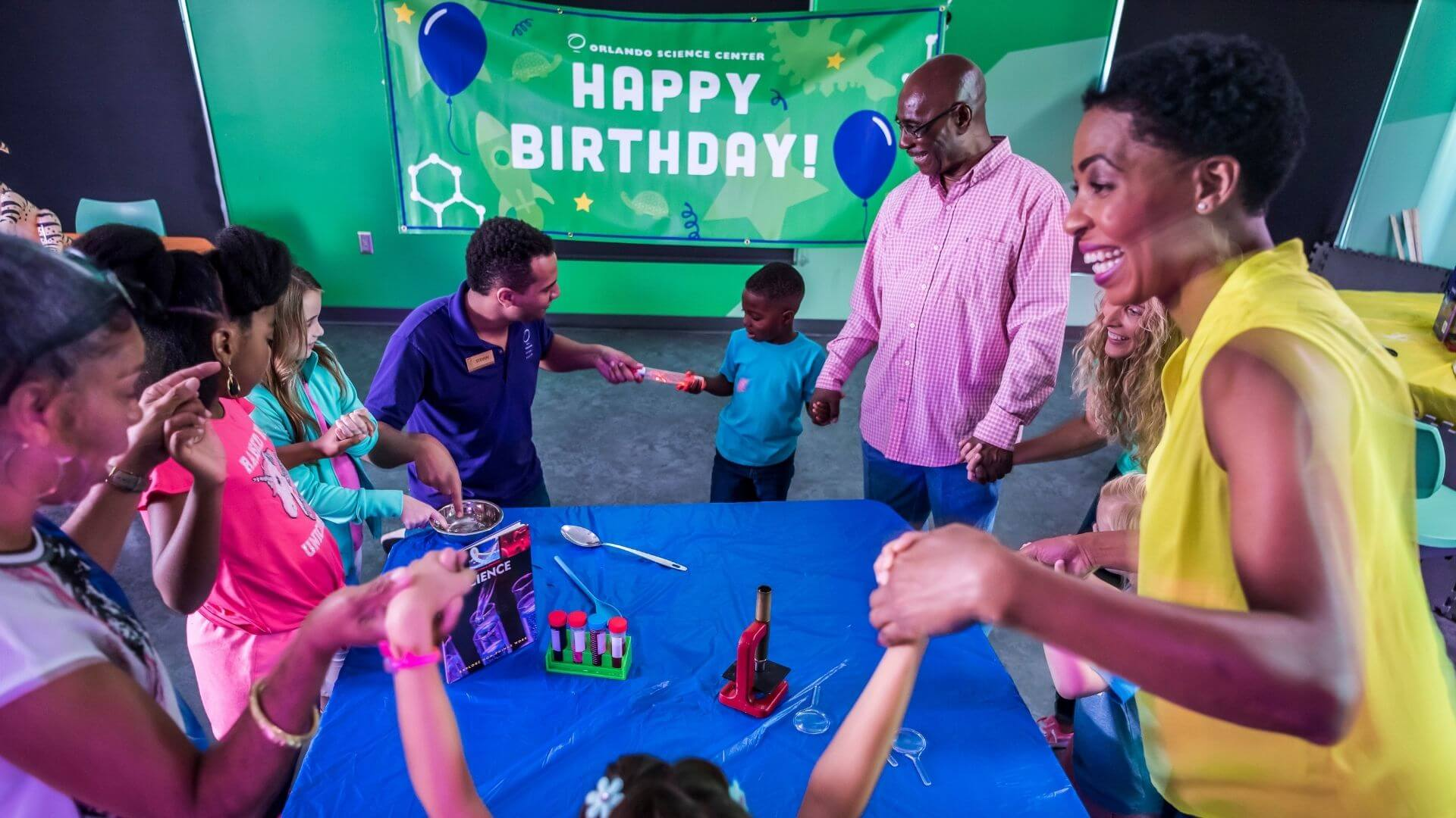 a group of kids and adults at a birthday party doing an experiment conducting electricity