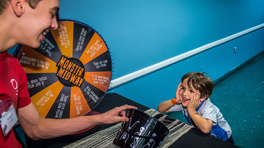 Child participating in scary-themed trivia wheel activity.