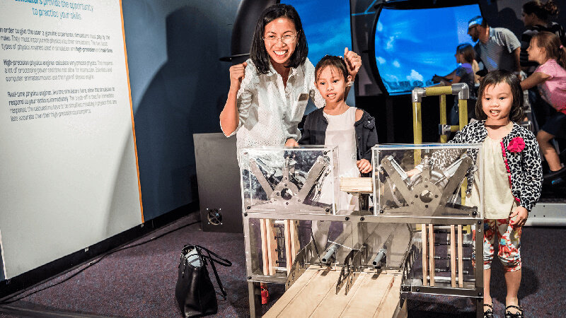 A caregiver and two young children race air cars in Kinetic Zone exhibit.