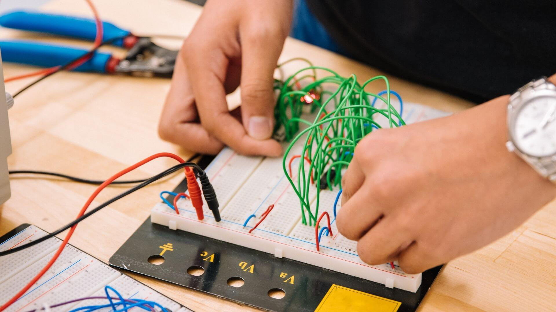 a teen working with wires on a computer